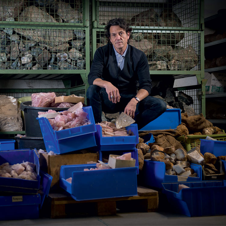 An image of gem hunter Stephen Webster sitting on a pile of rocks and gems
