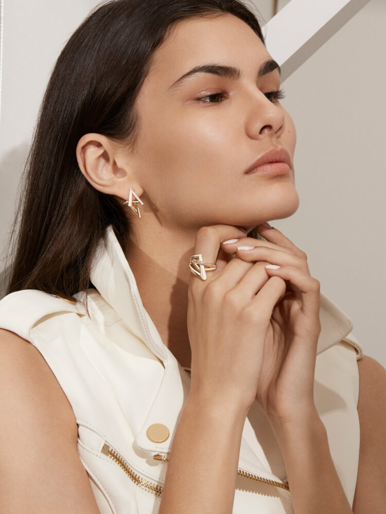 The Vertigo Acute Earrings and Obtuse Ring in white diamond and yellow gold on model.